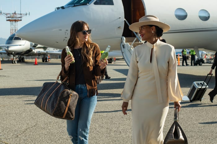 Maggie (Dakota Johnson) offers Grace Davis (Tracee Ellis Ross) two options of green juice, which I pray does not spill onto that pristine Victoria Beckham dress.