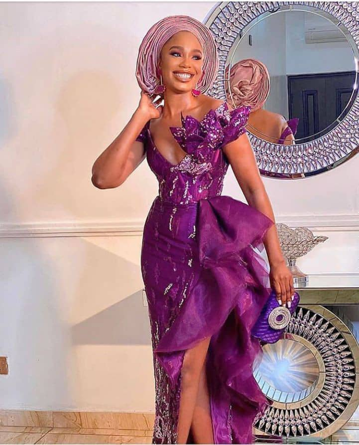 lady in a purple lace aso ebi gown