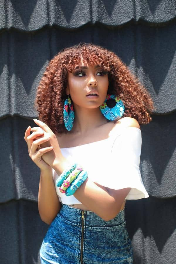 pretty lady wearing ankara earrings and bangle with jeans skirt