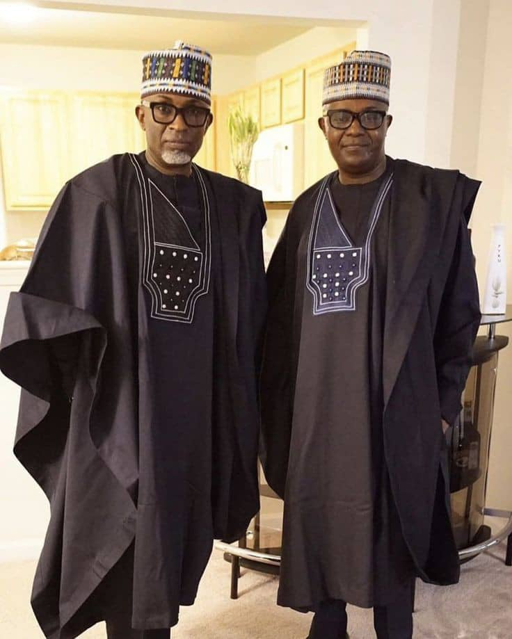 2 celebrity men wearing black agbadas with native caps