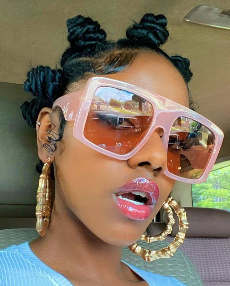 lady wearing big glasses and earrings with African hairstyle